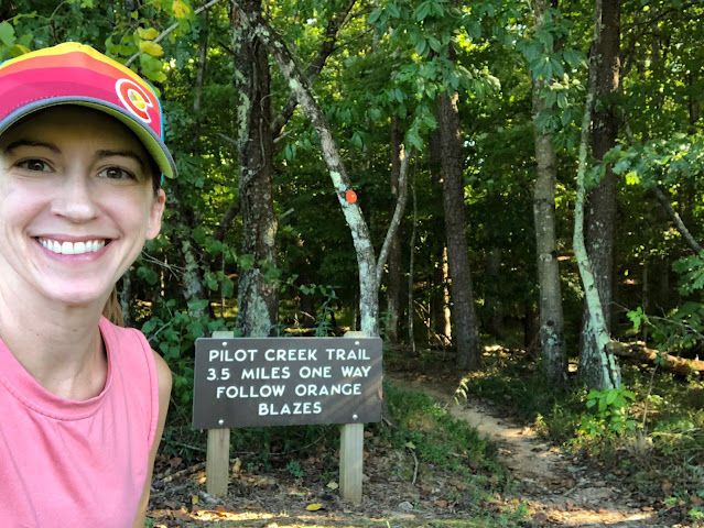 woman in front of trail sign