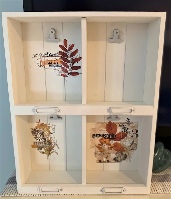 Photo of a white shadowbox with fall decor transfers in the back.