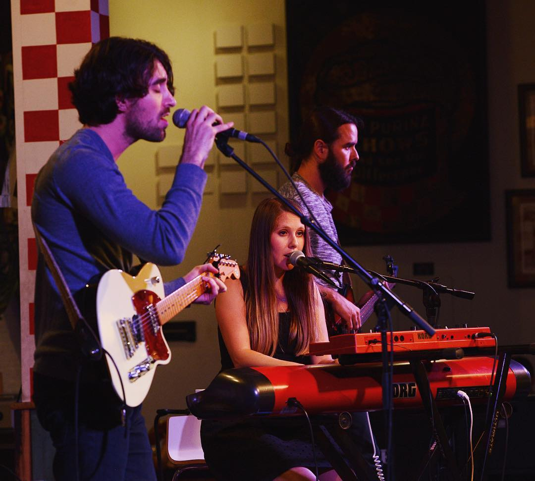 A live stage closeup of three people, the left one is holding a guitar and singing, the middle one is playing a keyboard piano and the right one playing a guitar.