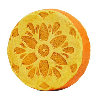 A circular puck shaped bath bomb with an intricate diamond lattice patter with blue pink and orange in the middle whilst the bomb is gold on a bright background