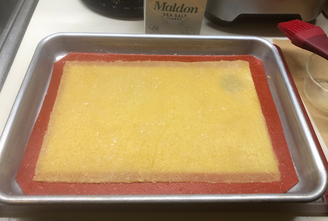 Photo of unbaked keto cheese crackers on silicone mat in small baking pan