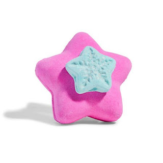 A big pink star shaped bath bomb with small silver spherical bath bombs in the middle with a yellow little star bomb on top on a bright background