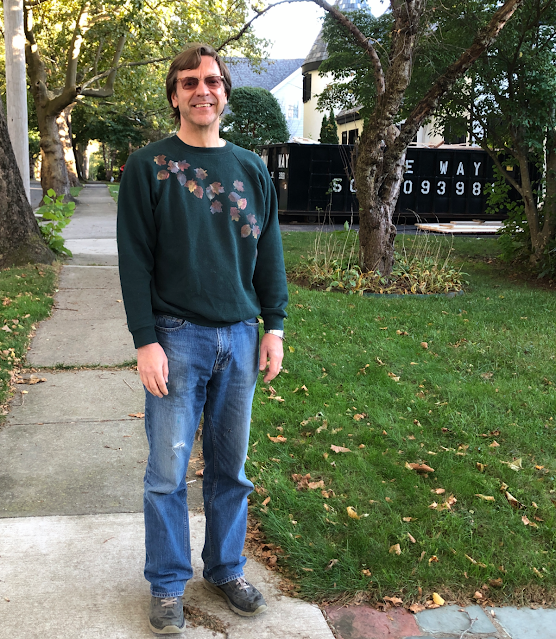 Photo of man wearing dark green sweatshirt with a stenciled metallic leaf design