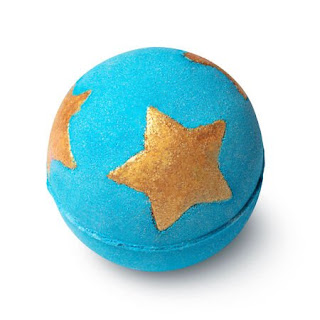 A blue spherical bath bomb with a hexagonal bottom with lush engraved into it with bright gold cocoa butter stars on a bright background