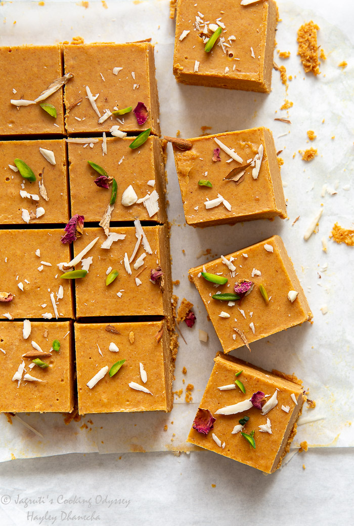 Overhead shot of square gujarati magas garnished with pisctachio, almond slivers and rose petals