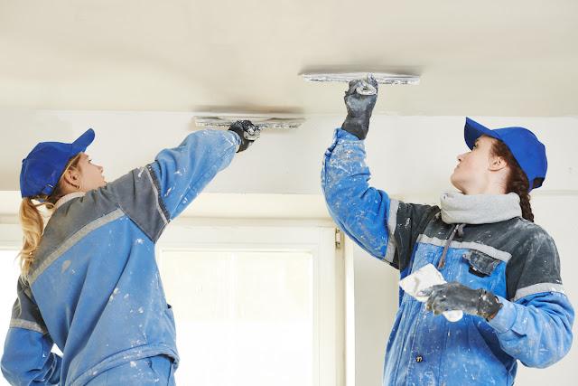 Workers skim coat ceiling