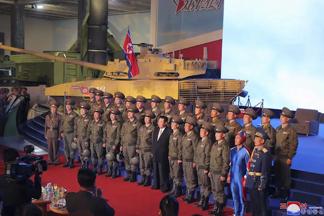 North Korean soldiers dressed in blue (second from right) in a photo taken with Chairman Kim Jong-un at the opening of the National Defense Exhibition in Pyongyang on October 11. Photo: KCNA