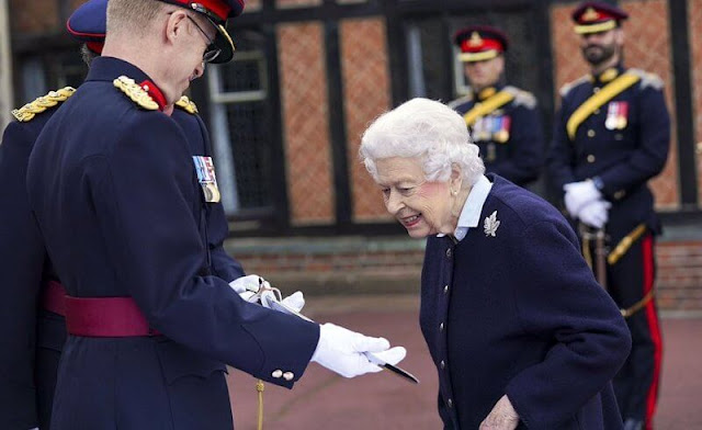 Queen Elizabeth wore a navy jacket over a blue shirt and a tweed skirt, accesorising with the Canadian diamond maple leaf brooch