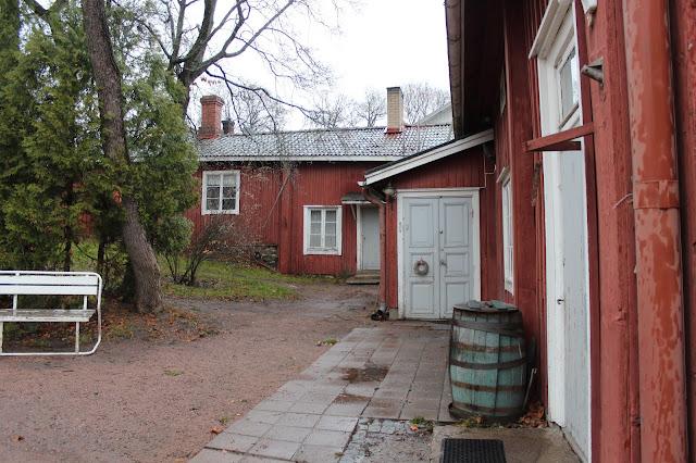 Vanha pihapiiri. Punamullatut rakennukset ympäröivät pihaa kahdella sivulla. Keskellä kasvaa vanha suuri puu.