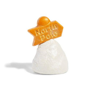 A white pyramid mound like shaped bubble bar with a golden sign above it in gold lustre with North Pole embedded into it on a bright background