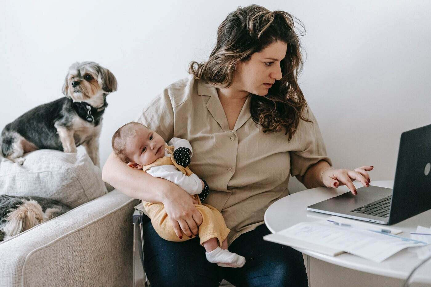 mom holding baby while working on laptop - helpful hints to make your way back to the workforce