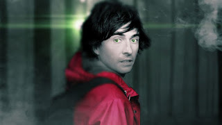 Man with green eyes and red coat looking scared in a forest