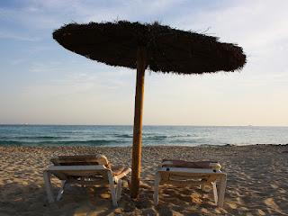 Thatch umbrella over beach chaise lounges