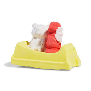 A yellow rectangular sleigh with a white bear and a red and white mini santa shaped bath bomb on a bright background