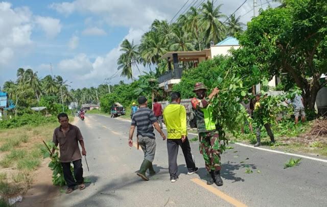 Babinsa Agung Sucianto Gotong Royong Bersama Warga Bersihkan Ranting Kayu Yang Menjurus ke Jalan Raya