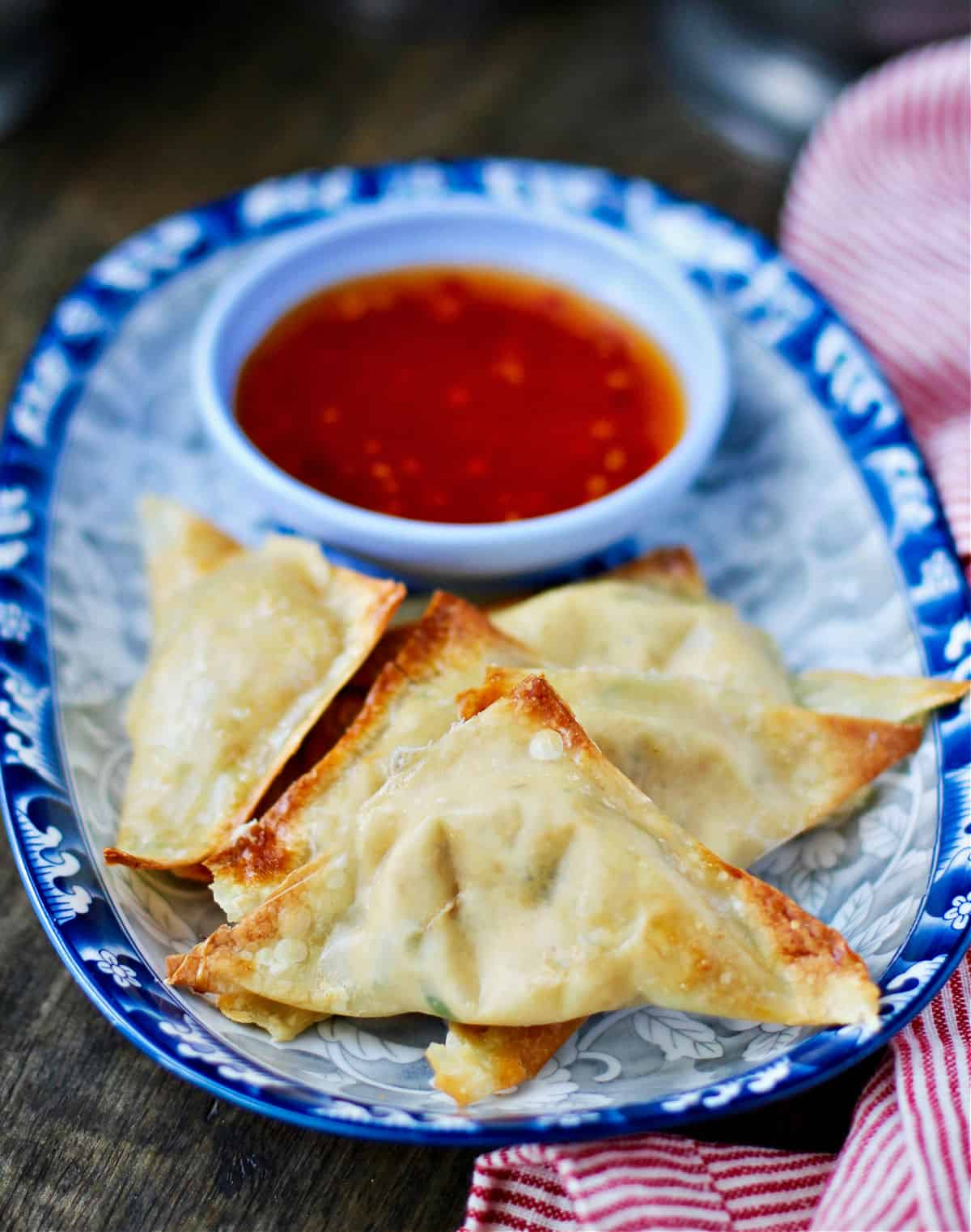 Crab rangoon on a plate with dip.