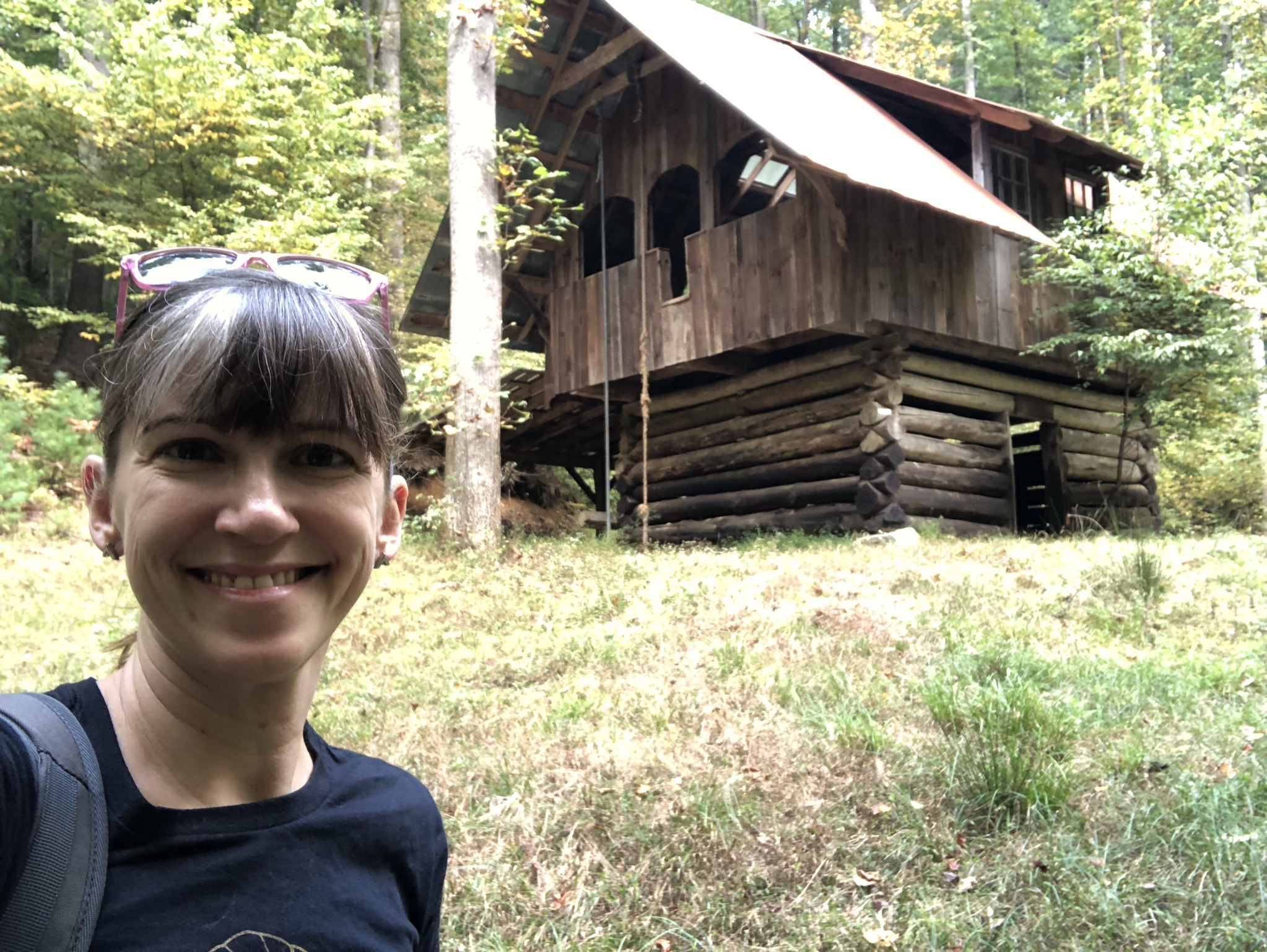 woman in front of cabin the woods