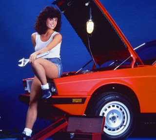 Betsy Russell posing for a picture with a car