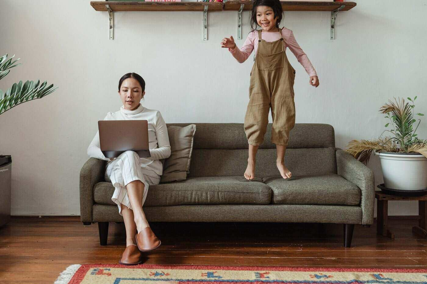 mother working on couch while daughter jumps - mom as a paid labourer