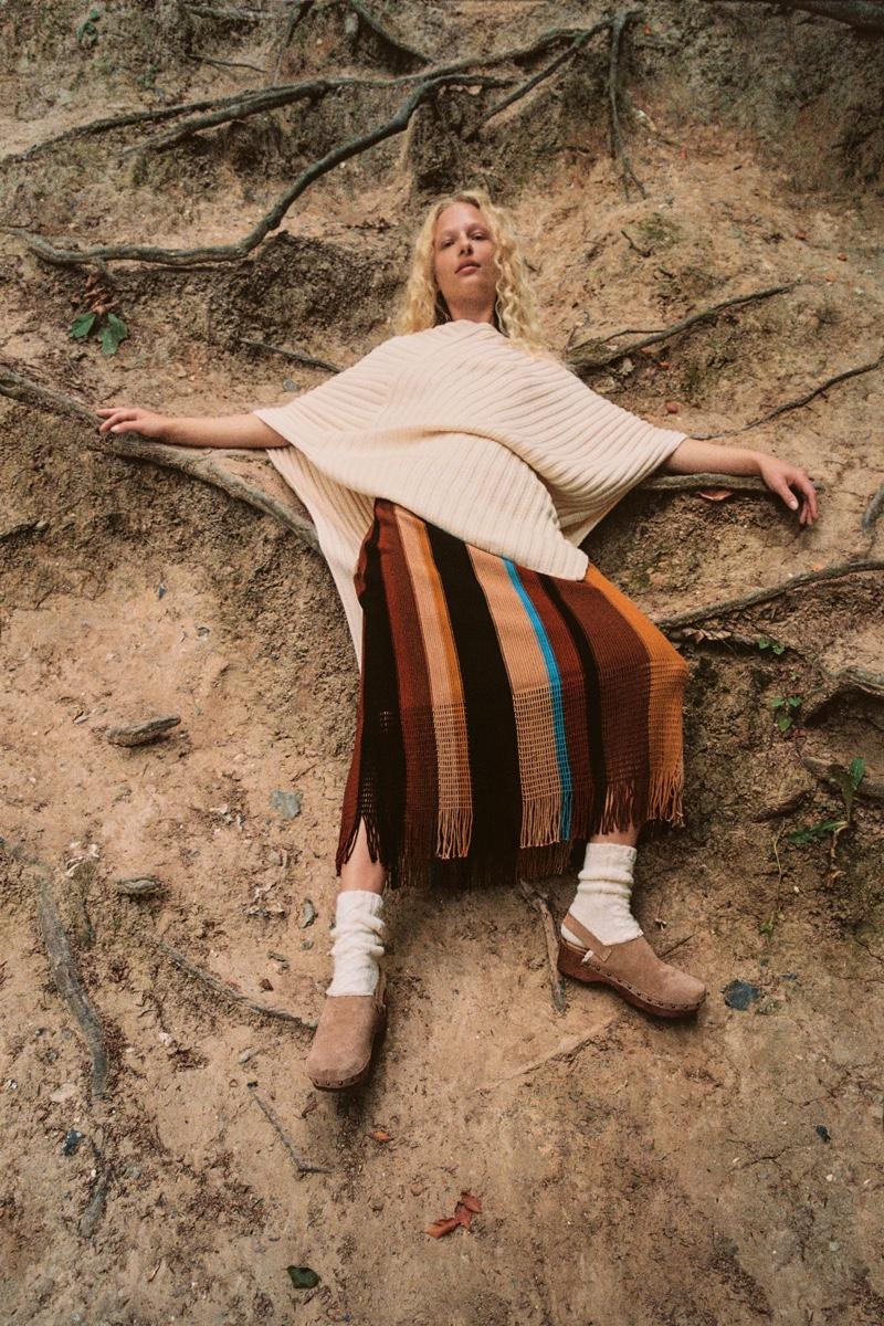 Frederikke Sofie models Zara Asymmetric Long Cape, Striped Knit Skirt, and Split Leather Clogs.