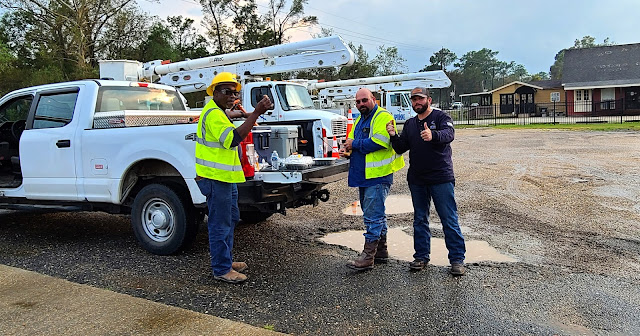 Three electrical workers standing in front of white work trucks.