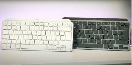 The silver logitech mx keys mini wireless keyboard next to the black version of the same