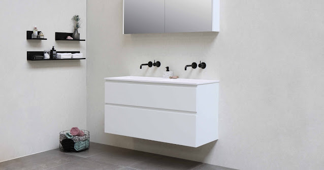 Dark fixtures at a white wall-mounted vanity in the bathroom.