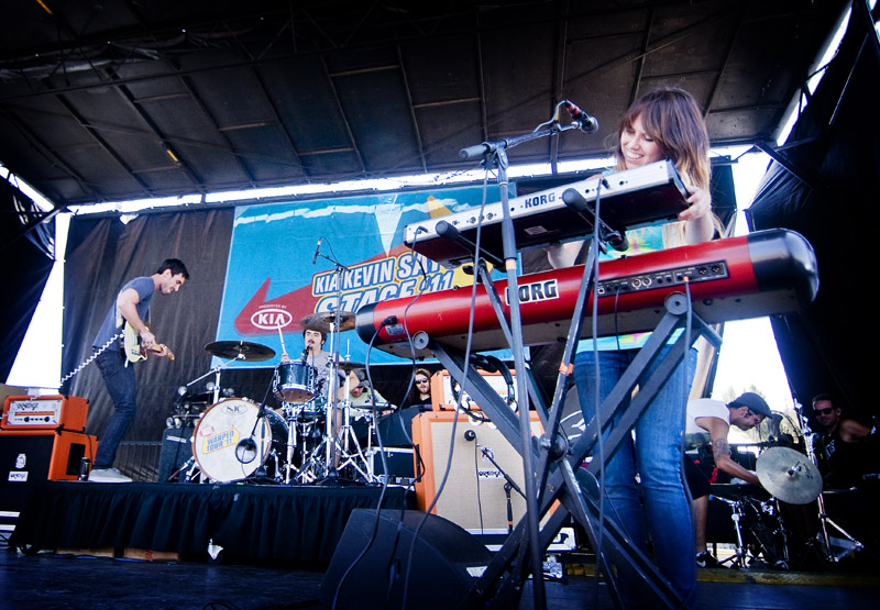 A band playing on a stage with a banner in the background in blue with orange letter says 'Kia Kevin Says Stage'