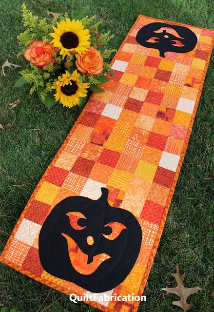 two black pumpkin faces on orange fabric squares
