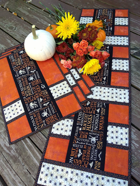 Fall flowers and mini pumpkins on a set of placemats and runner