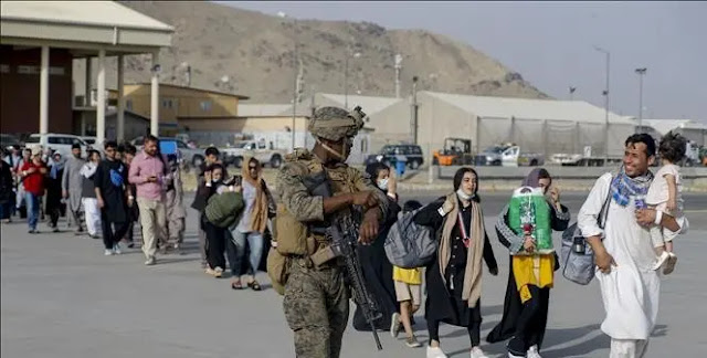 U.S. soldiers assist people to evacuate from Afghanistan, at Hamid Karzai International Airport in Kabul August 18, 2021. Photo: AFP