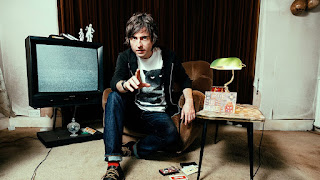 Danny Robins, kneeling down in front of a TV showing white noise