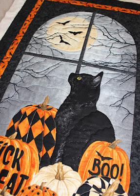 black cat with pumpkins, a moon, and bats