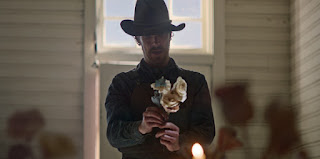Benedict Cumberbatch cowboy holding a bunch of white flowers
