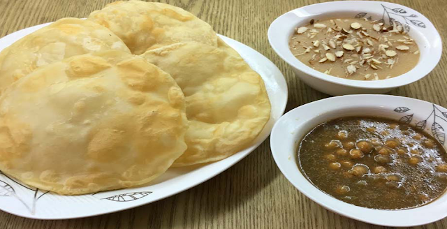 What is the complimentary with Halwa Puri?