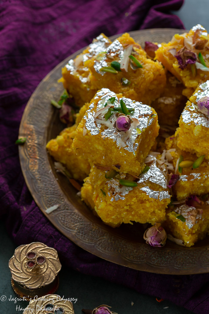 Close shot up of kalakand made using paneer, milk powder and pumkin served in a brass tray with purple napkin.