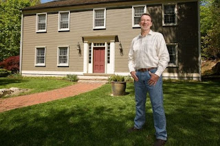 Elise Hauenstein's husband posing for picture in front of a house