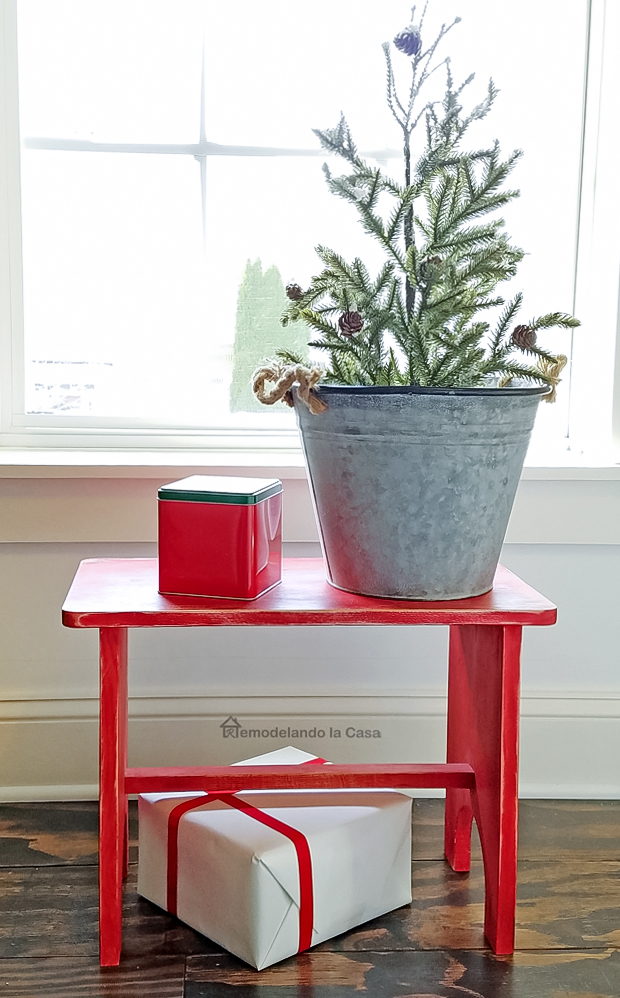 little red stool with Christmas tree by the window