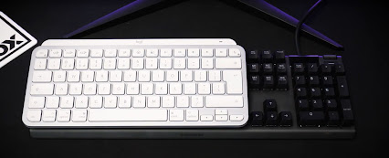 The logitech MX keys mini keyboard ontop of a full size keyboard for sizing reference