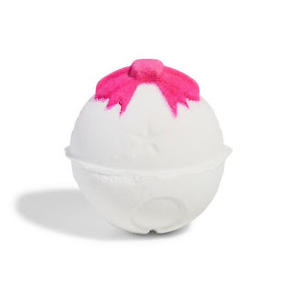 A bright spherical white bath bomb with a intricate circular design all over with a 3d red bow on top with blue sat in it on a bright background
