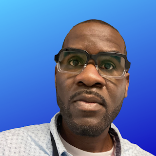 Photo of a Black man wearing glasses and a white shirt on a blue gradient background