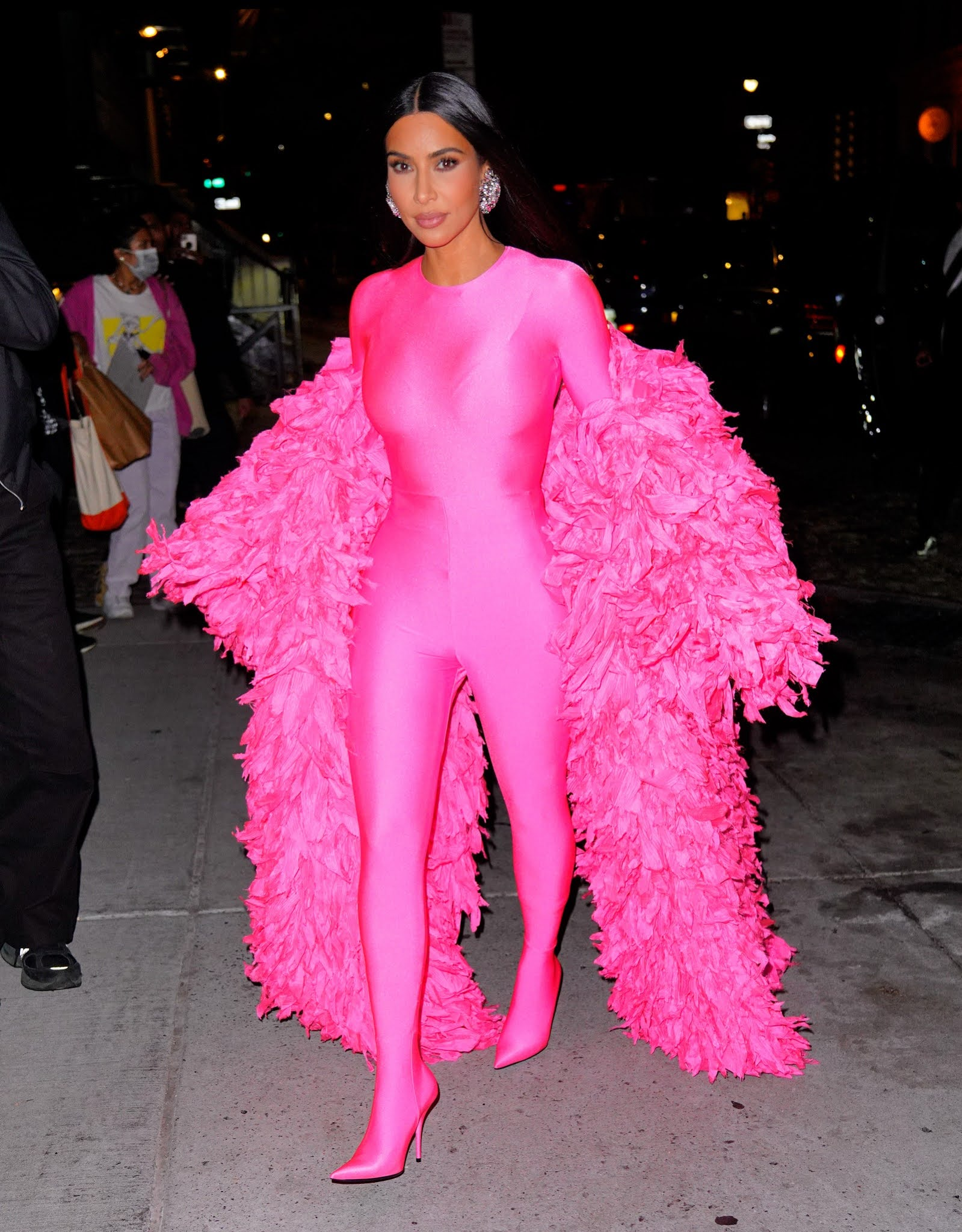 Kim Kardashian puts on eye-popping display in a skintight pink spandex catsuit and matching ruffled cloak as she heads to the SNL afterparty following first-ever hosting gig