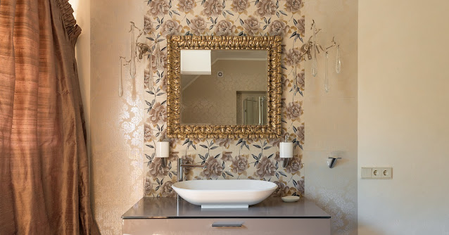 Floral wallpaper on the wall behind the vanity in a beige bathroom.