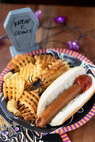 The vegan severed hot dog on a plate with waffle fries and some seasonal decor.