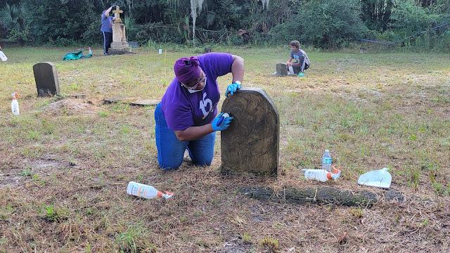 Dana Jones from Unity cleaning a headstone at the Pinehurst and San Sebastian Cemeteries Restoration Day