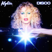 Kylie with big hair, green eyeshadow and a glittery background