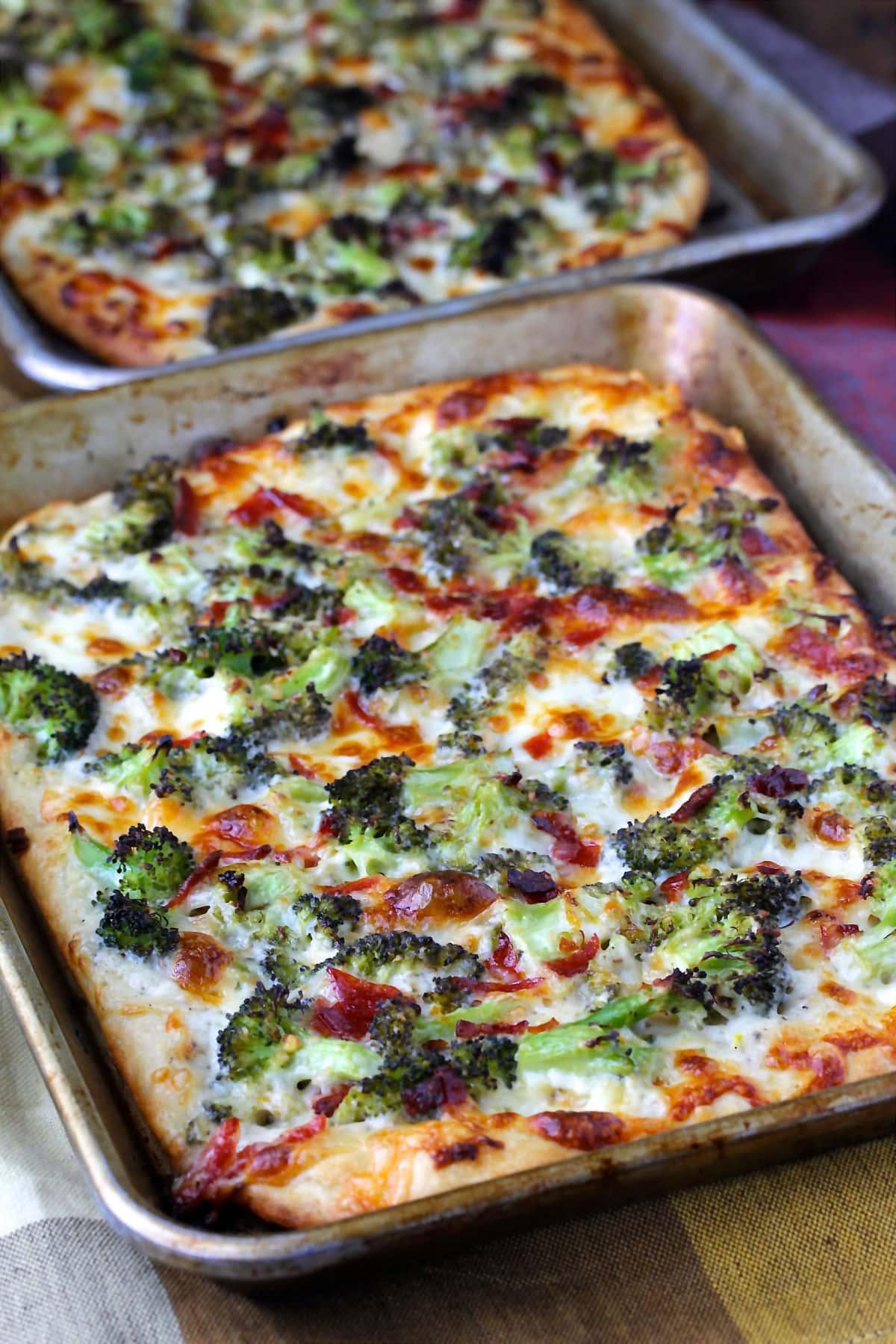 Broccoli Pizza with Provolone, Mozzarella, and Pecorino Romano in two pans.