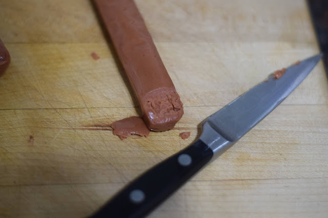 A nail bed being cut into the tip of the hot dog.