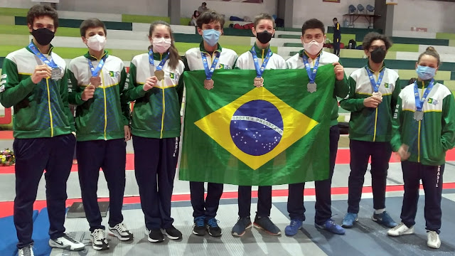 esgrimistas do Brasil seguram bandeira e mostram medalhas