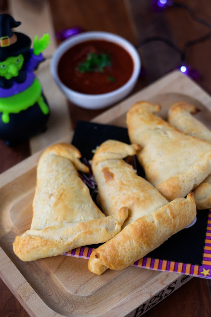 The Easy Vegan Witch Hat Hot Pockets on a cutting board with Halloween decor all around.